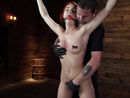 Smiling redhead model Lacey Lennon gets turned on with bondage