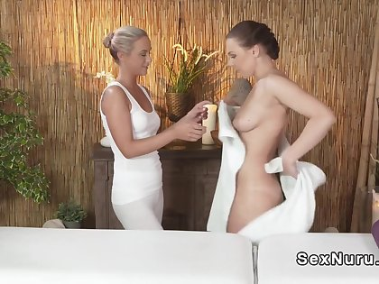 Blonde masseuse relaxing and rubbing brunette